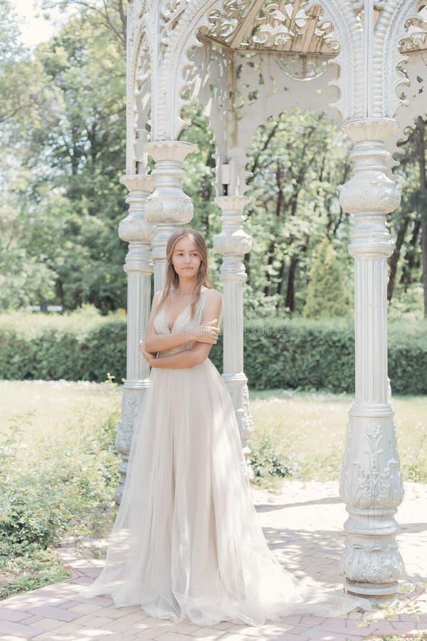 Het mooie gevoelige bruid sexy meisje in een lichte beige huwelijkskleding loopt in de tuin heldere zonnige warme dag royalty-vrije stock afbeelding