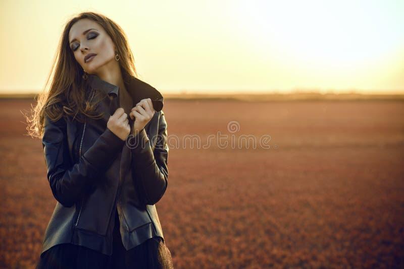 Het mooie glammodel met lang haar die het zwarte versluieren dragen kleedt zich en modieus leerjasje die zich op het verlaten geb stock foto's