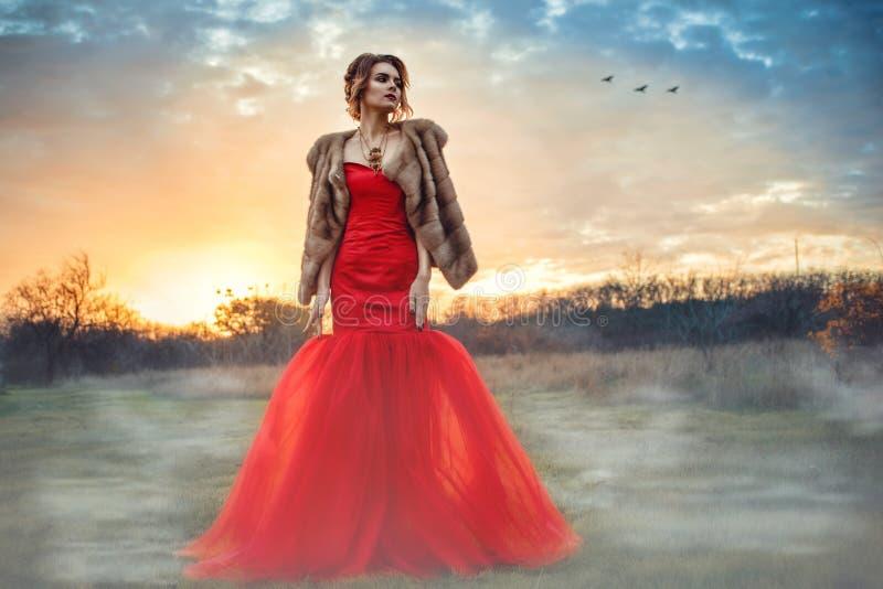 Het mooie glammodel met updohaar die elegante rode fishtail kleding dragen en de luxueuze mink bekleden status in het nevelige ge royalty-vrije stock foto's