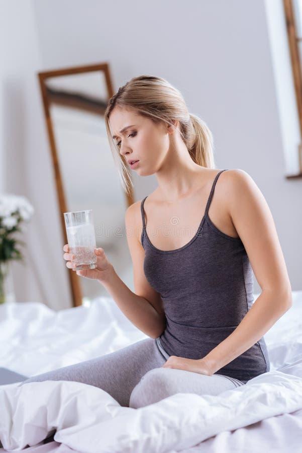 Het mooie glas van de vrouwenholding water met opgeloste tablet daarin stock afbeeldingen