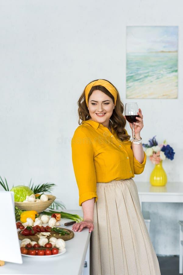 het mooie glas van de vrouwenholding van wijn en het bekijken groenten stock fotografie