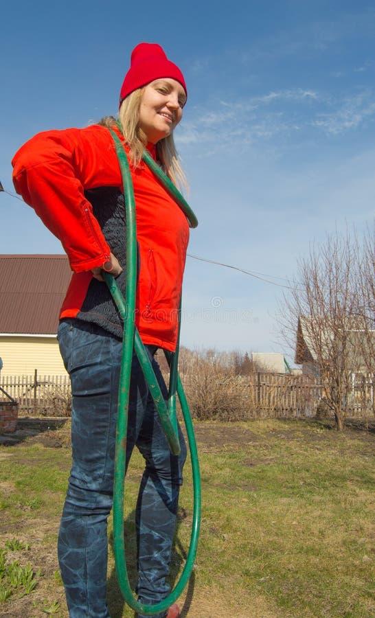 Het mooie het glimlachen landbouwersvrouw stellen in haar tuin die een een een het water geven slang, landbouw en ondernemerschap royalty-vrije stock fotografie