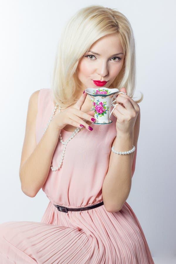 Het mooie glimlachende gelukkige sexy elegante meisje met rode lippenstift in een roze kleding in retro stijl drinkt theekoffie v stock foto