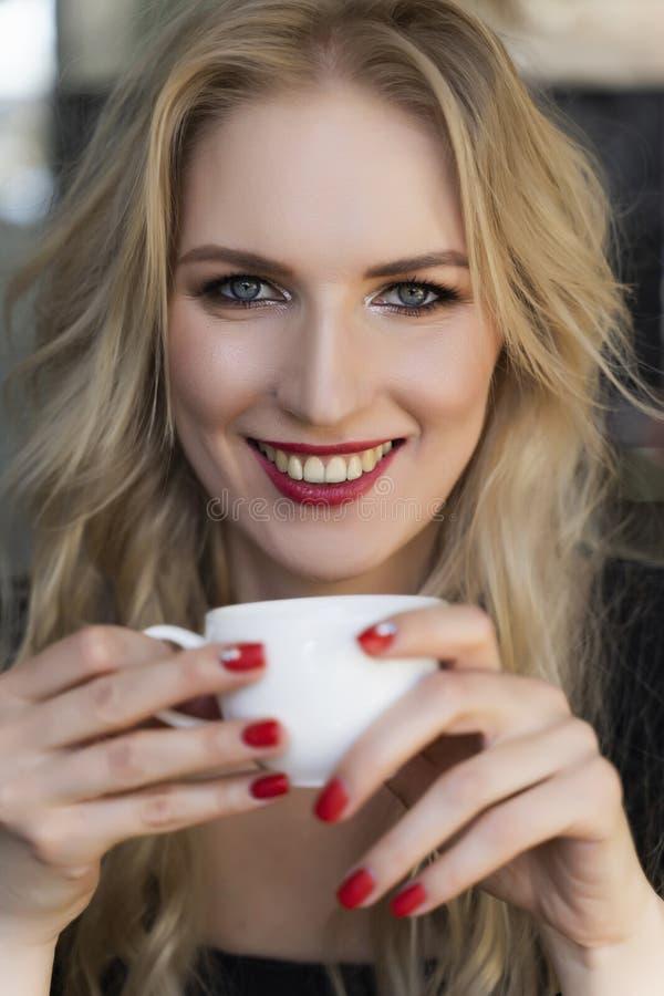 Het mooie glimlachende langharige blondemeisje zit en rust bij de lijst in koffie, houdend een kop van koffie in haar handen Slui royalty-vrije stock afbeelding