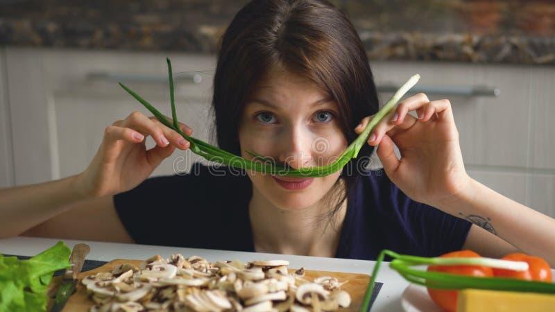 Het mooie grappige spel van de vrouwenkok met groene ui op lijst in keuken thuis stock foto