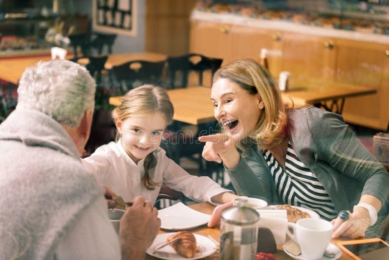 Het mooie grootmoeder lachen die aan haar kleindochter luisteren royalty-vrije stock afbeelding