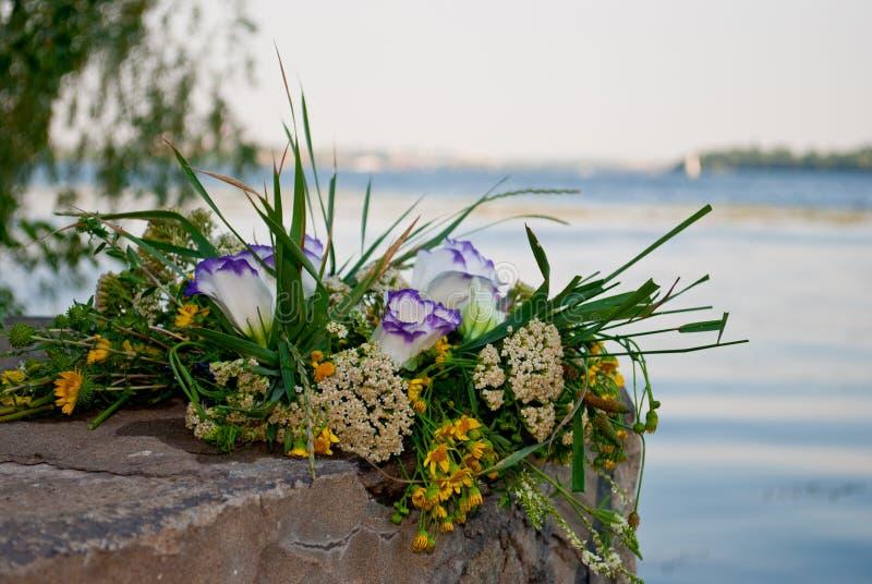 Het mooie grote boeket van bloemenkroon ligt op de stenen van de verschansing op de achtergrond van de rivier Ivan Kupala stock foto's