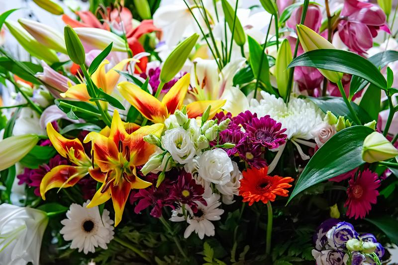 Het mooie grote boeket van chrysanten, de orchideeën en gerberas met een grote gele lelie in een bloem winkelen royalty-vrije stock foto