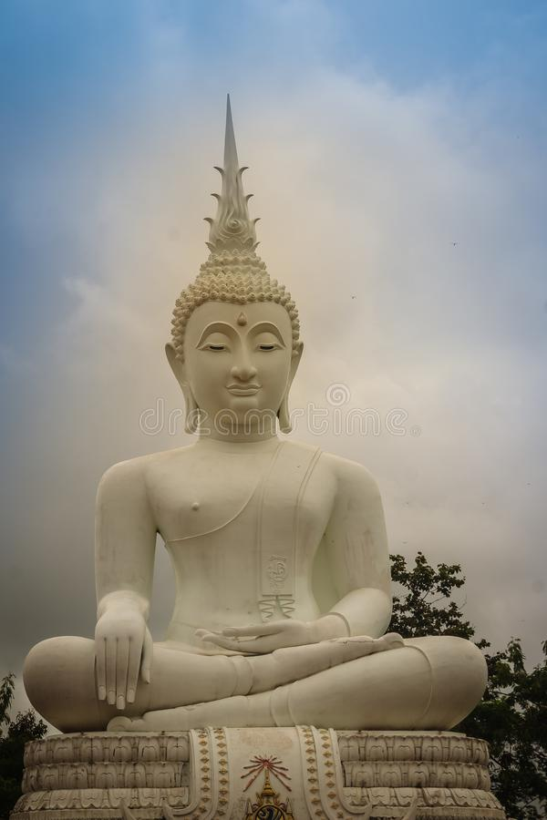 Het mooie grote witte standbeeld van Boedha tegen blauwe hemel en witte wolk bij de openbare bostempel, Wat Phu Phlan Sung, Nacha stock foto