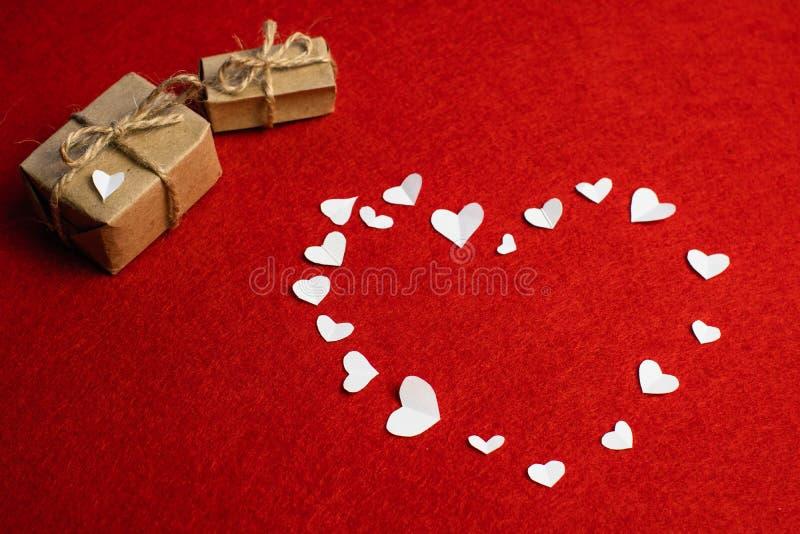 Het mooie hart maakte van klein Witboek heartsand twee die giften met bogen op rood worden geïsoleerd Heilige Valentine stock fotografie
