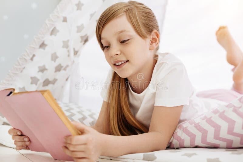 Het mooie heldere meisje concentreerde zich bij het opwekken van verhaal royalty-vrije stock afbeelding