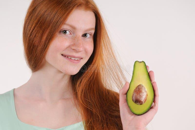 Het mooie het glimlachen jonge meisje stellen met de helft van avocado stock foto's