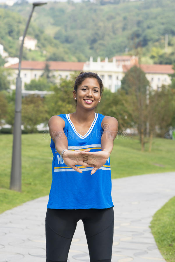 Het mooie het glimlachen sportieve vrouw doen rekt zich alvorens a op te leiden uit stock foto's