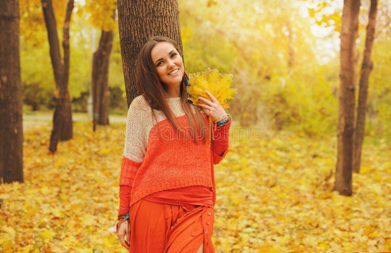 Het mooie het glimlachen vrouwenportret, die in de herfstpark lopen, kleedde zich in toevallige oranje sweater en rok stock afbeeldingen