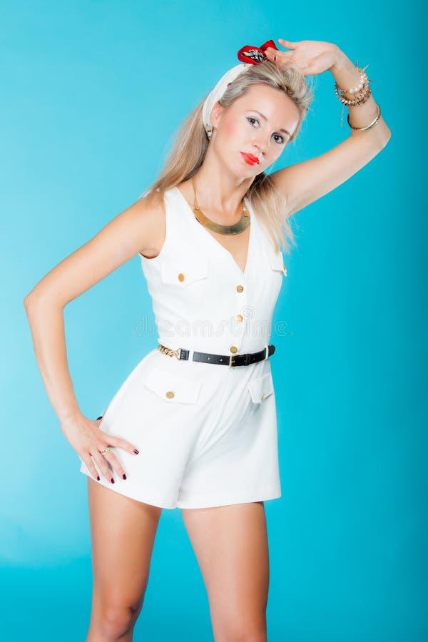 Het mooie het meisjes retro stijl van de blondevrouw pinup stellen op blauw stock foto's