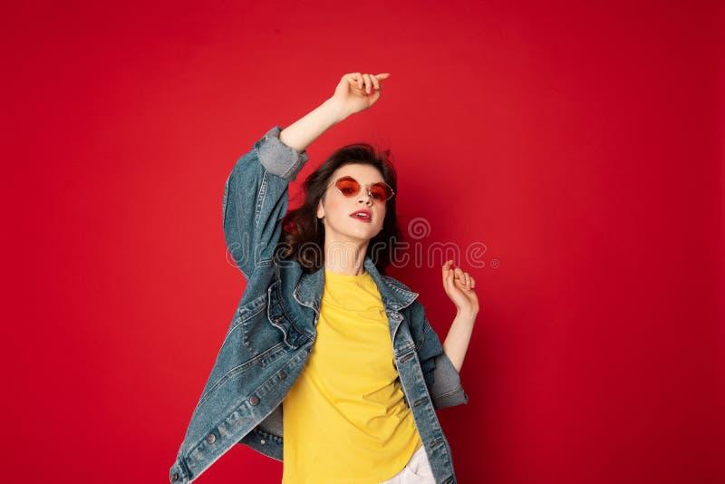 Het mooie hipstermeisje stellen ge?soleerd op rood royalty-vrije stock foto