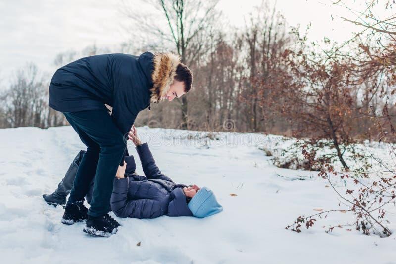 Het mooie het houden van paar spelen in de winter bosmens holding en het duwen meisje in sneeuw Mensen die pret hebben in openluc royalty-vrije stock afbeeldingen