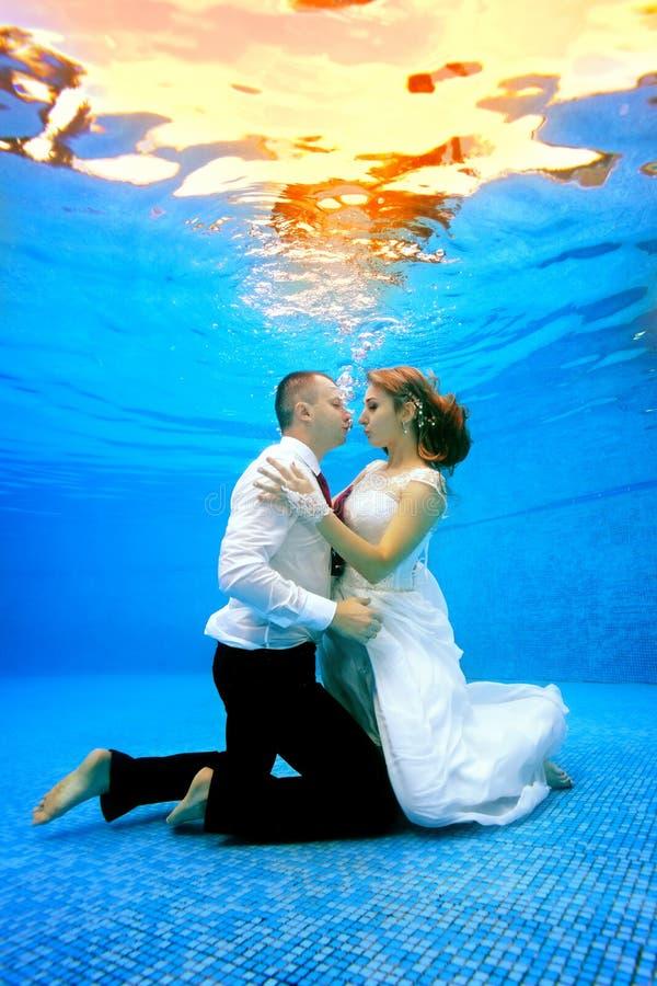 Het mooie houdende van paar in huwelijk kleedt tribunes op haar knieën onderwater bij de bodem van de pool royalty-vrije stock foto's