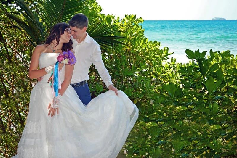 Het mooie houdende van paar van jonggehuwden is tribune op het strand Huwelijk en wittebroodsweken in de keerkring op het Eiland  royalty-vrije stock afbeeldingen