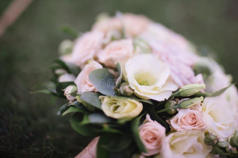het mooie huwelijksboeket van witte bloemen ligt op het gras stock fotografie