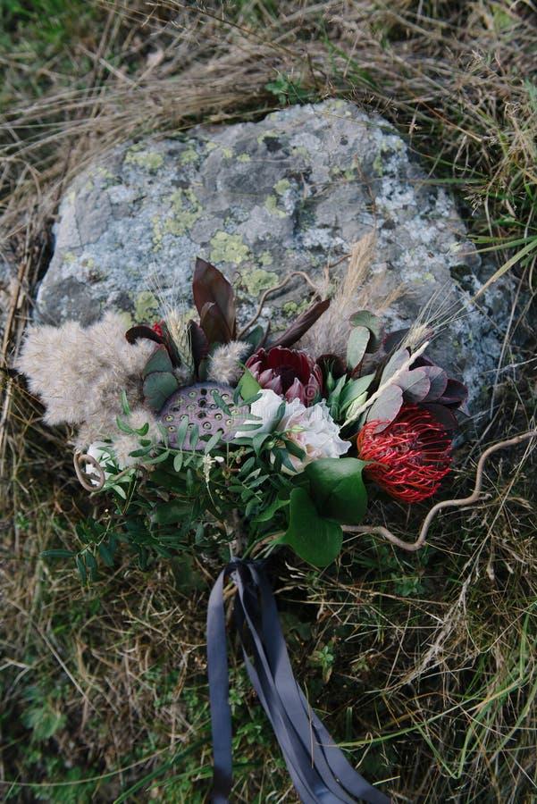 het mooie huwelijksboeket van witte bloemen ligt op het gras royalty-vrije stock afbeeldingen