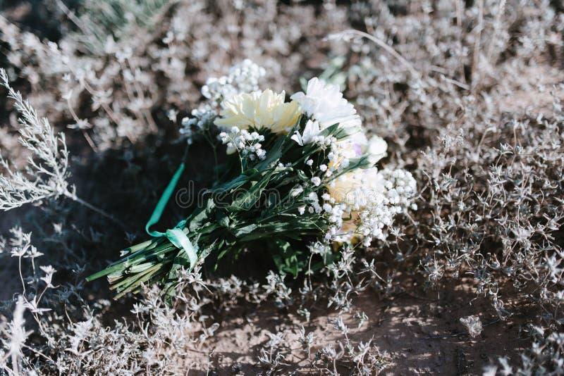 het mooie huwelijksboeket van witte bloemen ligt op het gras royalty-vrije stock foto's