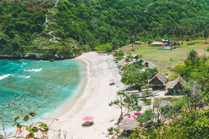 Het mooie idyllische witte strand die van zandatuh verzoeken om ontspant Duidelijke blauwe oceaangolven die aan het strand rollen stock afbeelding