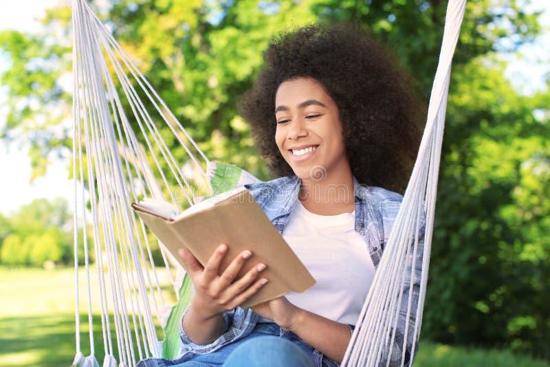 Het mooie jonge Afrikaans-Amerikaanse boek van de vrouwenlezing in hangmat in openlucht stock fotografie