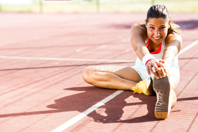 Het mooie jonge atletische vrouw uitrekken zich in de zomer stock afbeelding