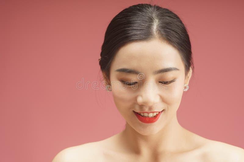 Het mooie Jonge Aziatische die portret van het Vrouwengezicht, op roze achtergrond wordt geïsoleerd royalty-vrije stock foto