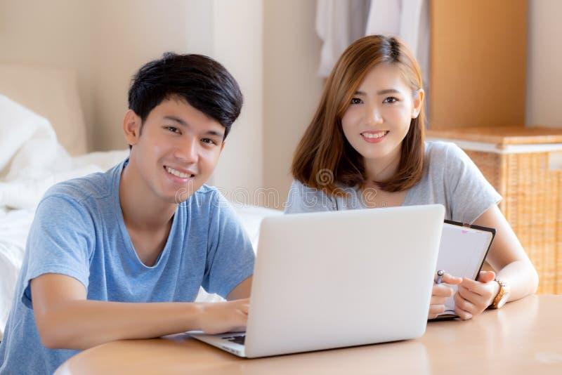 Het mooie jonge Aziatische paar berekent uitgavenfinanciën met laptop en samen planning, vrouw het schrijven notitieboekje stock afbeeldingen