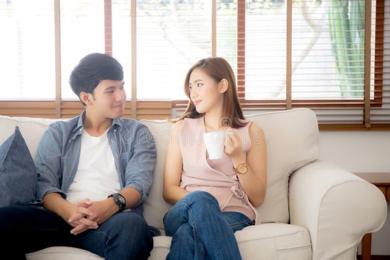 Het mooie jonge Aziatische paar thuis glimlachen en het spreken verhaal gehuwde zitting op bank stock foto's