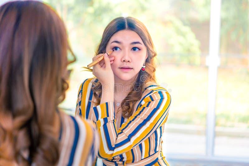 Het mooie jonge Aziatische vrouw zetten op haar maakt omhoog voor haar groter slaapkamervenster stock foto