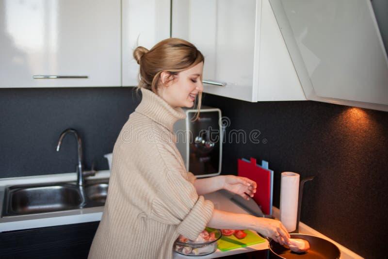 Het mooie jonge blonde kookt kip met groenten, zelf-kookt gezond voedsel royalty-vrije stock fotografie