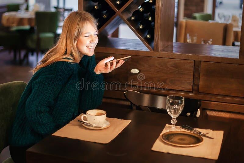 Het mooie jonge blonde met telefoon en kop van koffie glimlacht in koffieemoties van geluk royalty-vrije stock afbeelding