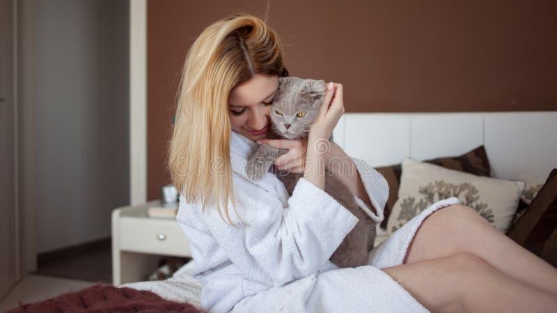 Het mooie jonge blondemeisje in een Badstof witte robe in haar flat koestert haar geliefde kat stock foto