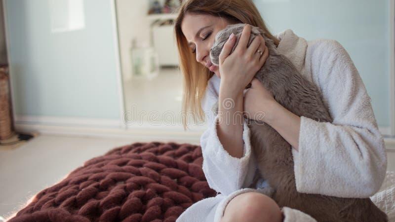 Het mooie jonge blondemeisje in een Badstof witte robe in haar flat koestert haar geliefde kat royalty-vrije stock foto