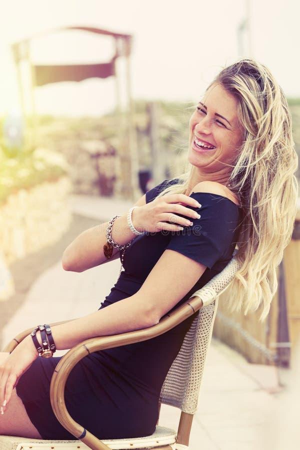 Het mooie jonge blondemeisje openlucht lachen stock foto