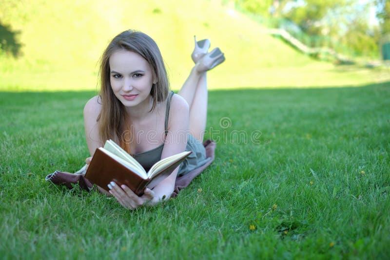 Het mooie jonge boek van de vrouwenlezing bij park royalty-vrije stock afbeelding