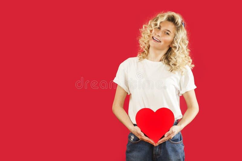 Het mooie jonge emotionele meisje met een rood hart in haar handen bevindt zich op een geïsoleerde rode achtergrond De dag van de stock fotografie