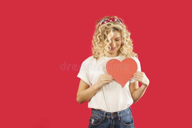 Het mooie jonge emotionele meisje met een rood hart in haar handen bevindt zich op een geïsoleerde rode achtergrond De dag van de stock afbeeldingen
