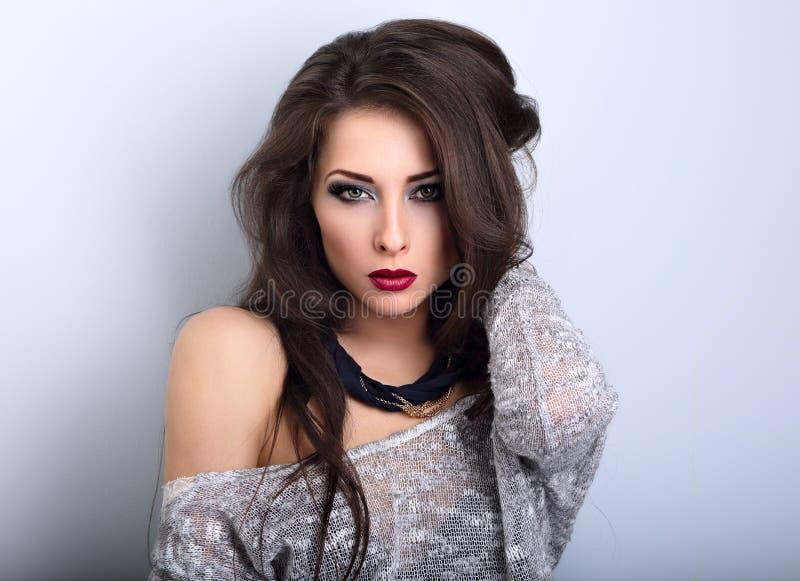 Het mooie jonge expressieve samenstelling model stellen in grijze blouse w stock fotografie