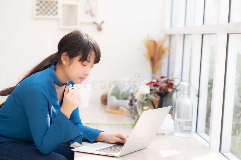 Het mooie jonge freelance Aziatische vrouw glimlachen die en aan laptop computer bij de winkel van de bureaukoffie met beroeps we stock afbeeldingen
