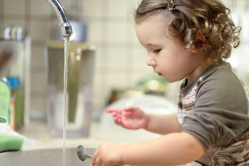 Het mooie jonge geitje wast schotels in keuken stock foto