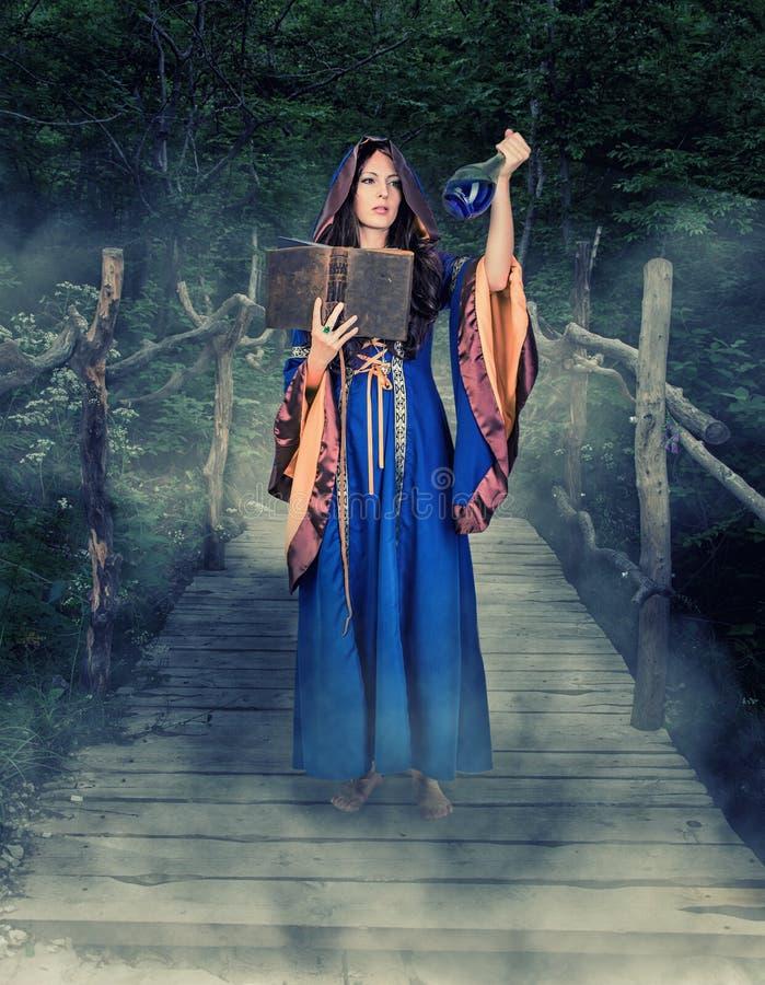 Het mooie jonge Halloween-heksenmeisje magisch gieten stock afbeeldingen