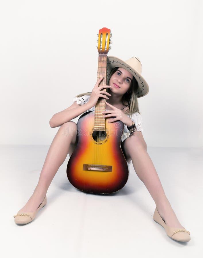 Het mooie jonge langbenige blonde meisje van het Land in een van de litl witte kleding en cowboy hoed met een gitaar stock fotografie