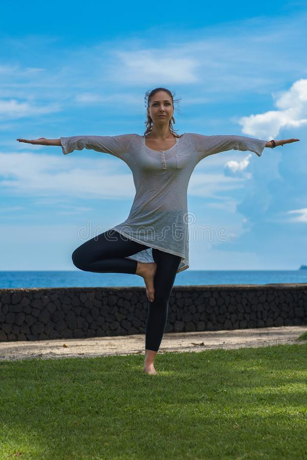 Het mooie jonge meisje in beenkappen en uniformjas maakt yogapraktijk, meditatie, die asana op het oceaanstrand Bali Indonesië be royalty-vrije stock fotografie