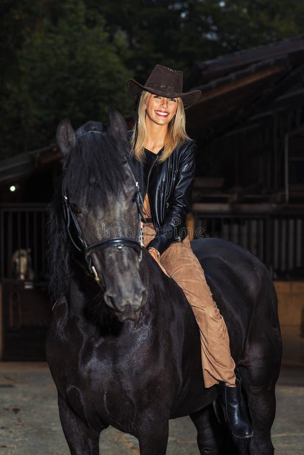 Het mooie jonge meisje berijdt haar bruin paard tijdens het berijden royalty-vrije stock foto