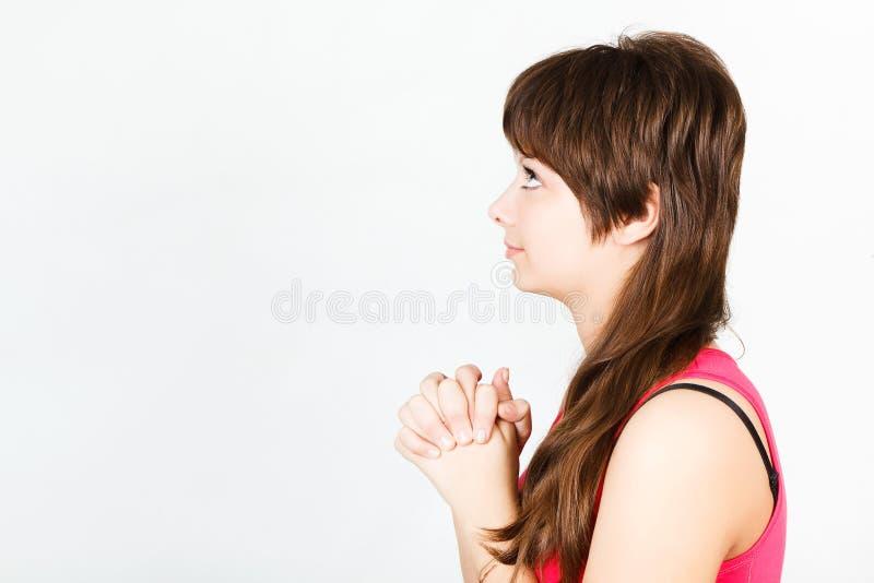 Het mooie jonge meisje bidt upwards het kijken stock fotografie