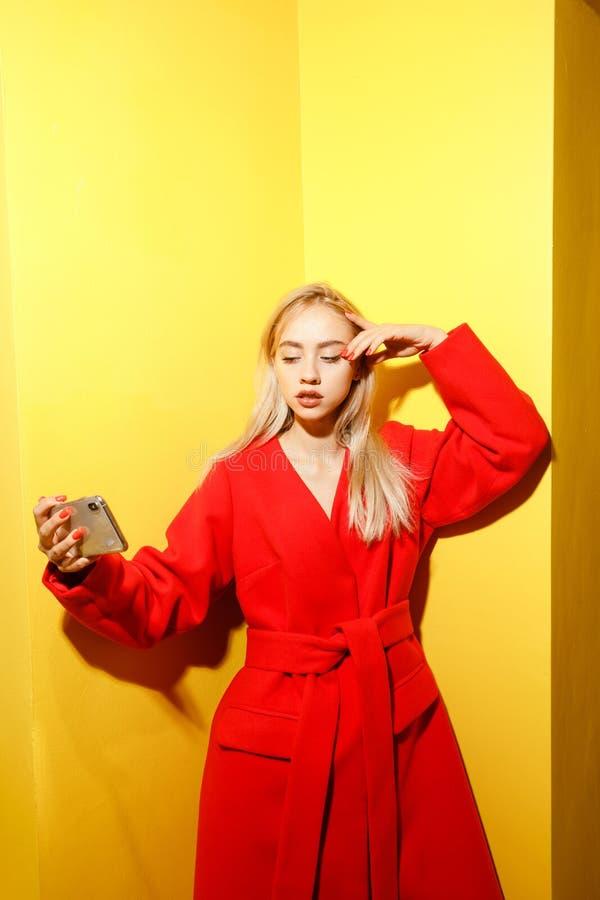 Het mooie jonge meisje blogger gekleed in modieuze rode laag neemt een selfie op haar smartphone op de achtergrond van geel royalty-vrije stock afbeeldingen